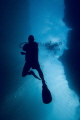 Diver swims through passage at Spooky Channel dive site in Roatan.