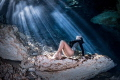 Freediver basking in the sun rays beaming through the surface of one of the many cenotes in the Riviera Maya, Mexico