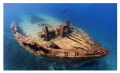 A skin diver swims down the port side of the wreck of the