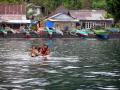 Children of Tandurusa Village playing on a makeshift raft, Lembeh Strait, North Sulawesi, Indonesia