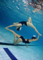 Connected. Synchro swimmers in a pool.