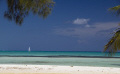 A sailboat passes by Cayman Kai, on the North shore of Grand Cayman.  The really small white dots on the horizon line are dive boats on the North wall.  A beautiful place to dive.  A beautiful place to
