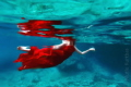 She is swimming in the sea with red dress and fresh water on the top side in the sea.